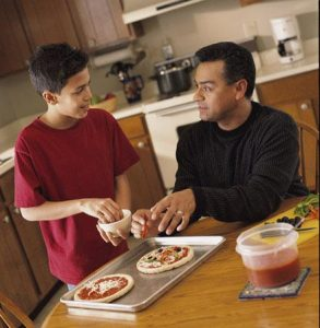 Father and son making pizzas.